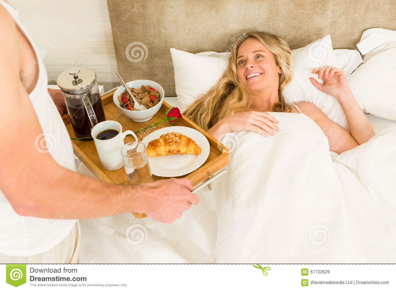 cute man bringing breakfast to his girlfriend stock image