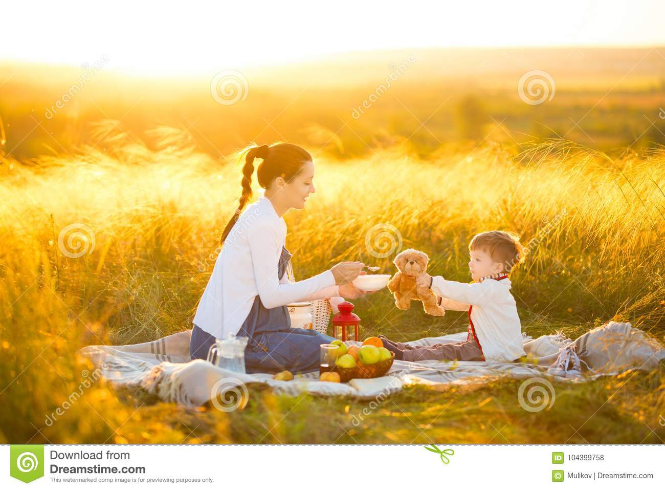 Cute mom and little son playing with my teddy. Mother and son feeding teddy bear on a picnic
