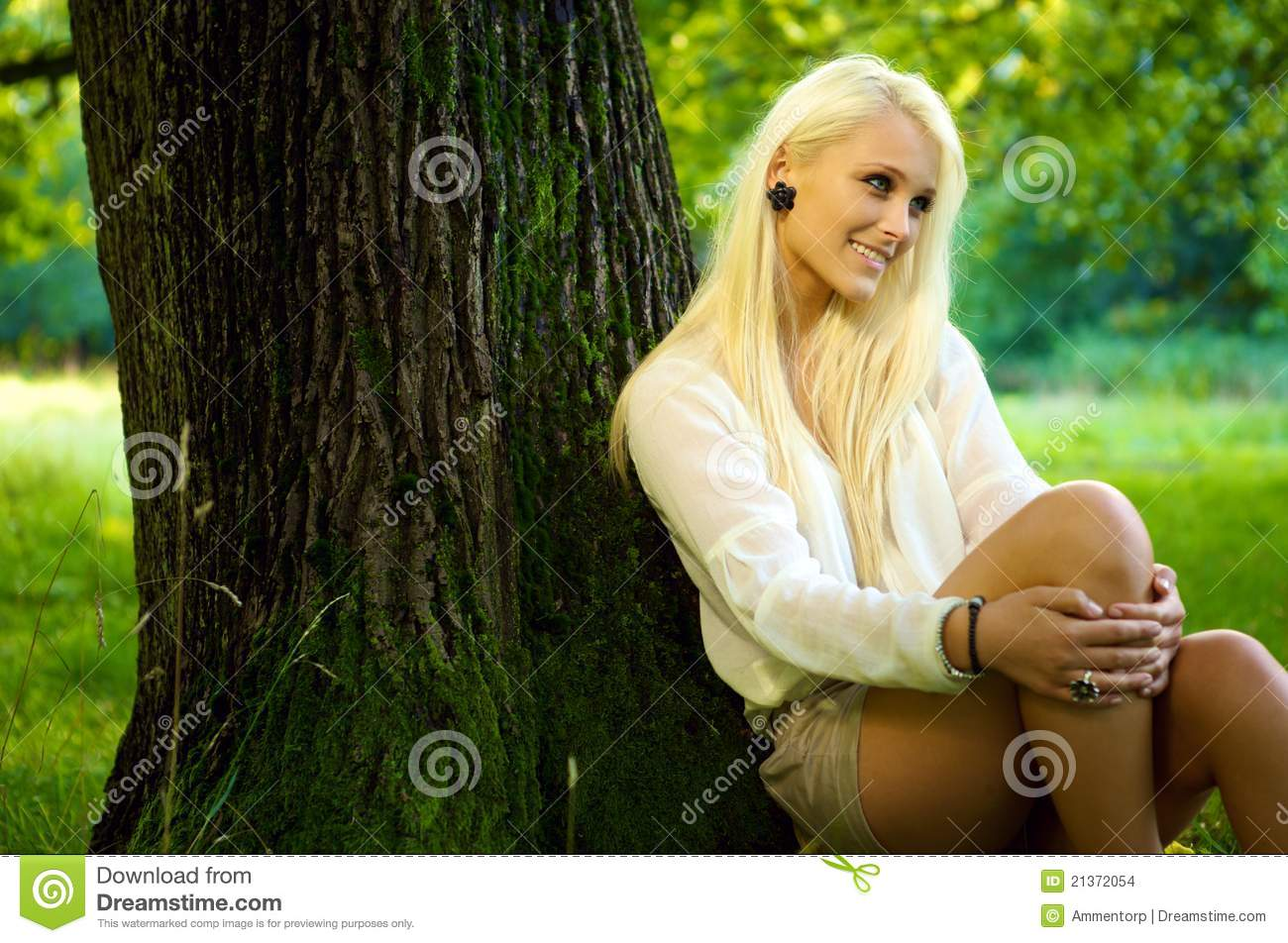 cute natural beauty relaxing against a tree stock photo - image of