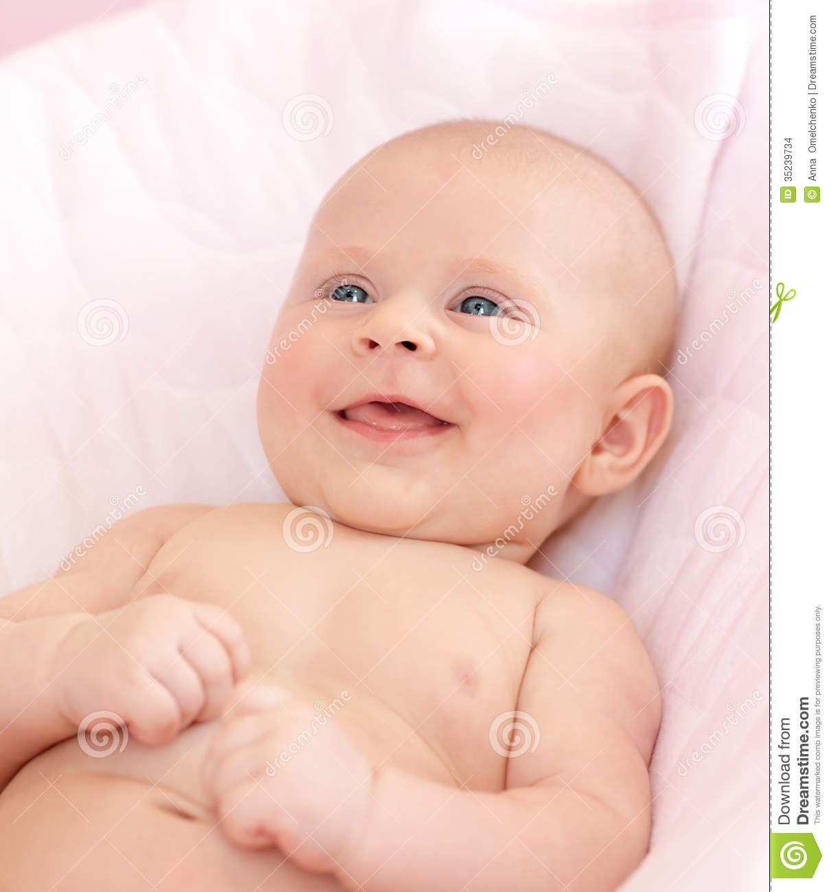 Closeup portrait of cute newborn baby lying down in the bed at home smiling face happy childhood health care new life concept