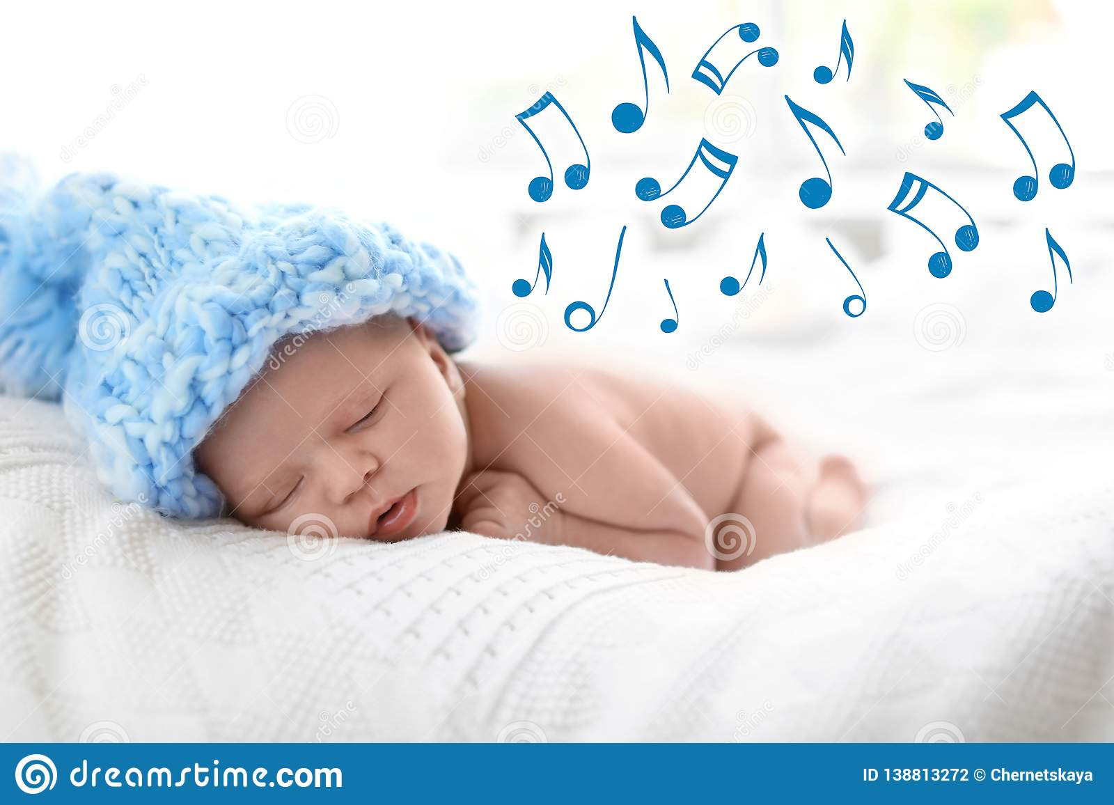 Cute newborn baby in knitted hat sleeping on bed and flying music notes.