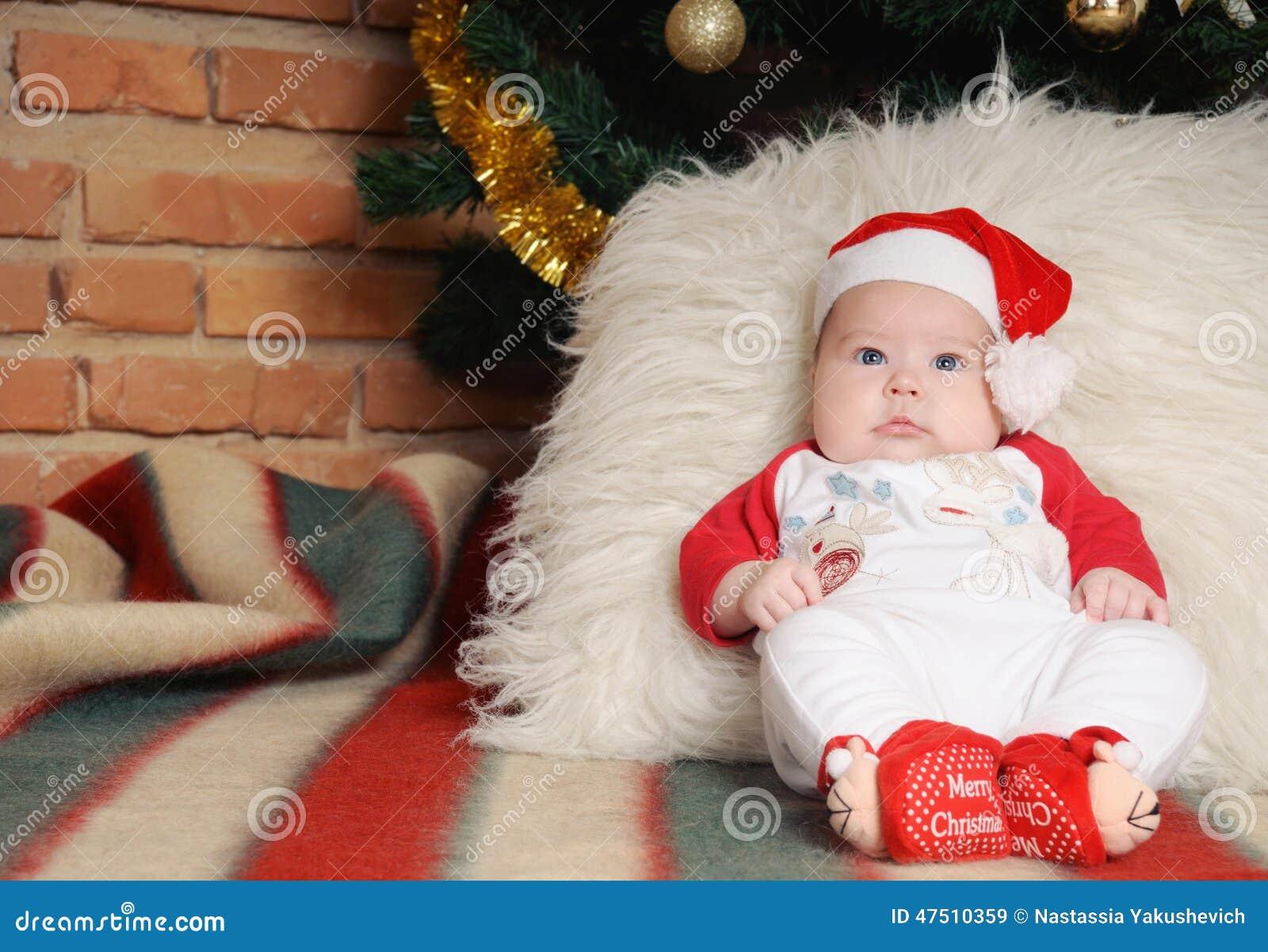 Cute newborn baby in santa hat sitting near christmas tree