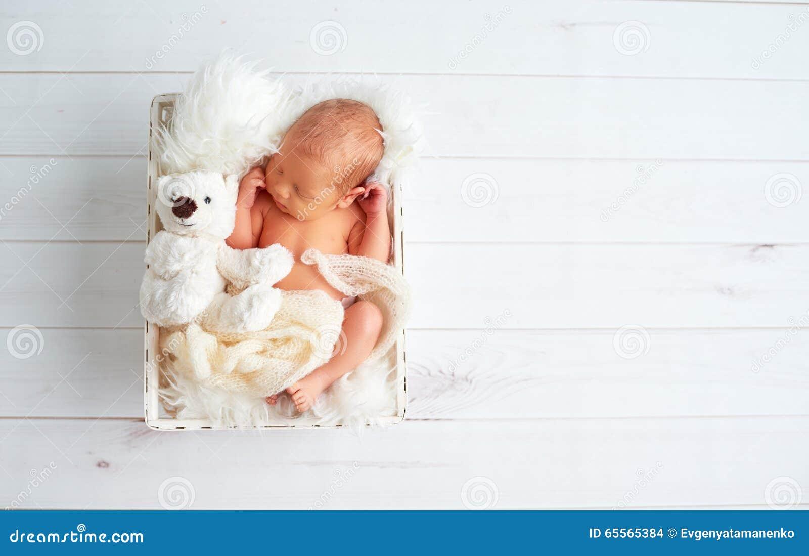 Cute newborn baby sleeps with toy teddy bear in basket