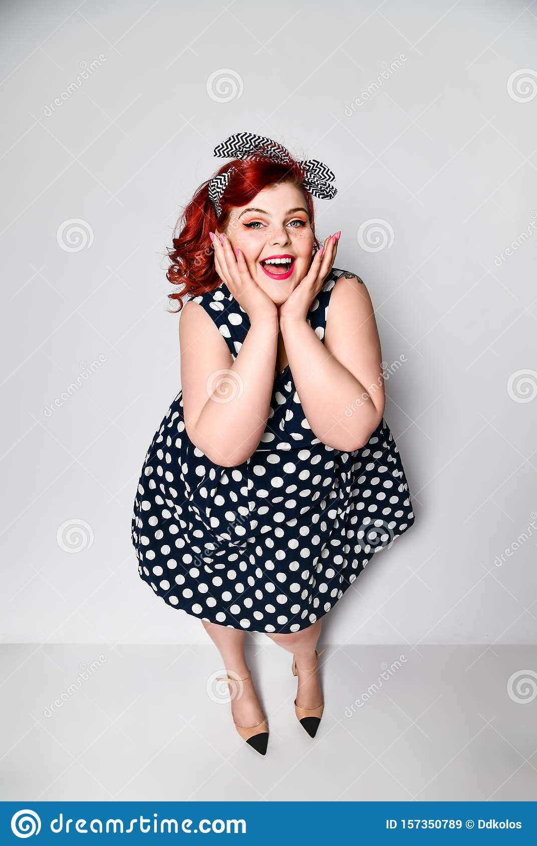 Pin up woman portrait. Beautiful retro female in polka dot dress with red lips and manicure nails and old fashion hairstyle