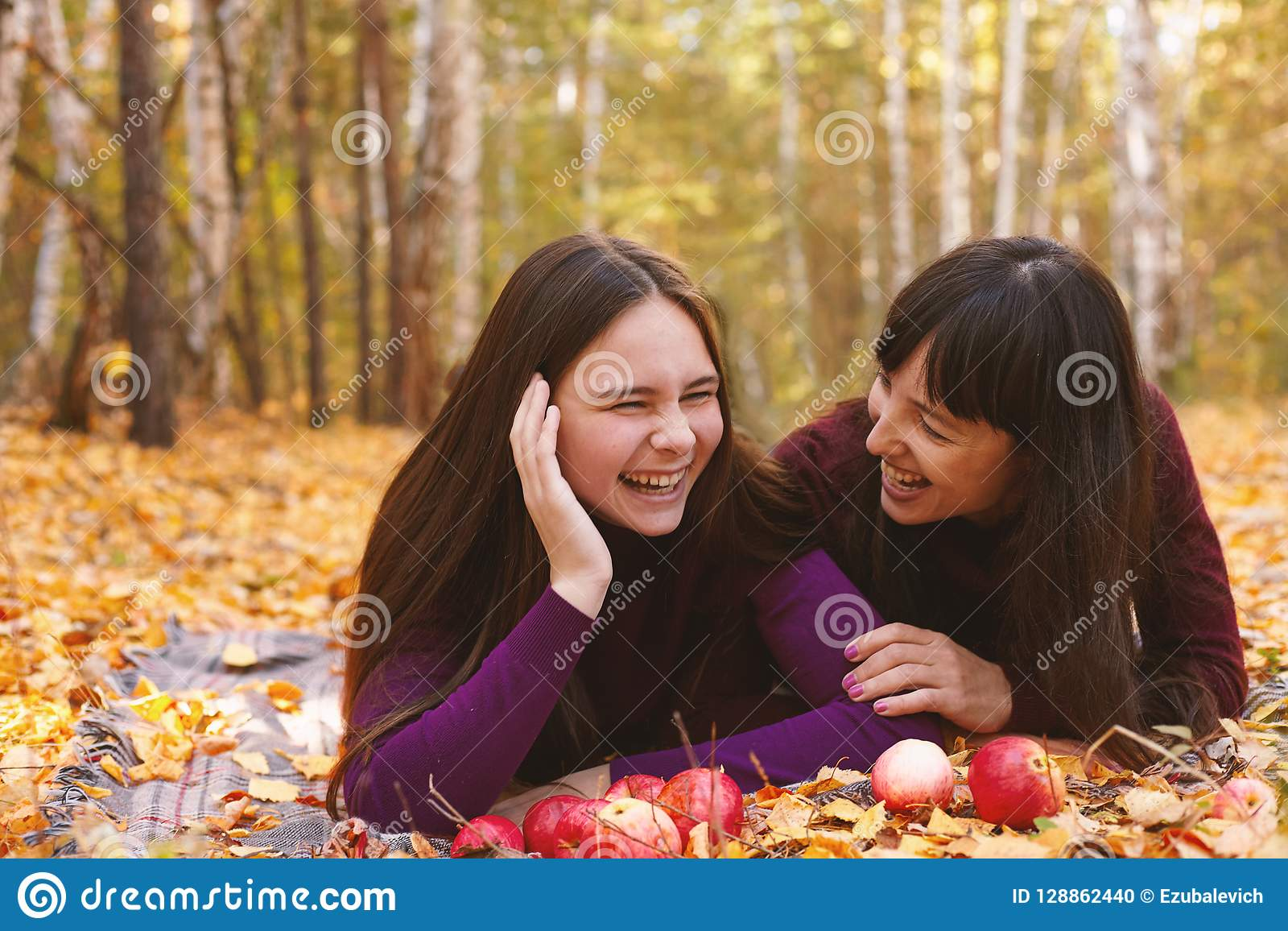 Cute portrait of mother and daughter in the autumn forest.