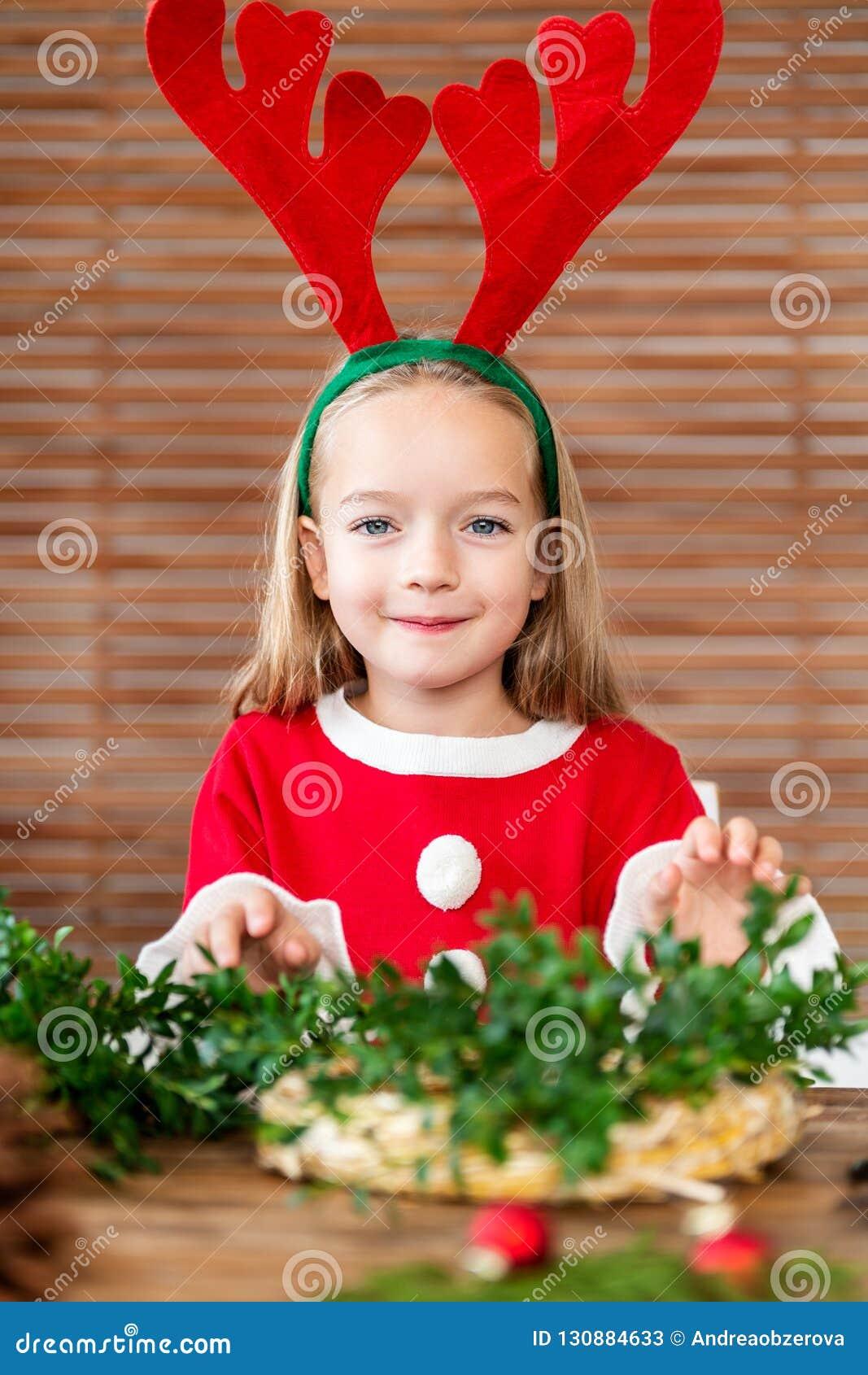 Cute preschooler girl dressed in reindeer costume wearing reindeer antlers making christmas wreath in living room. DIY Christmas.