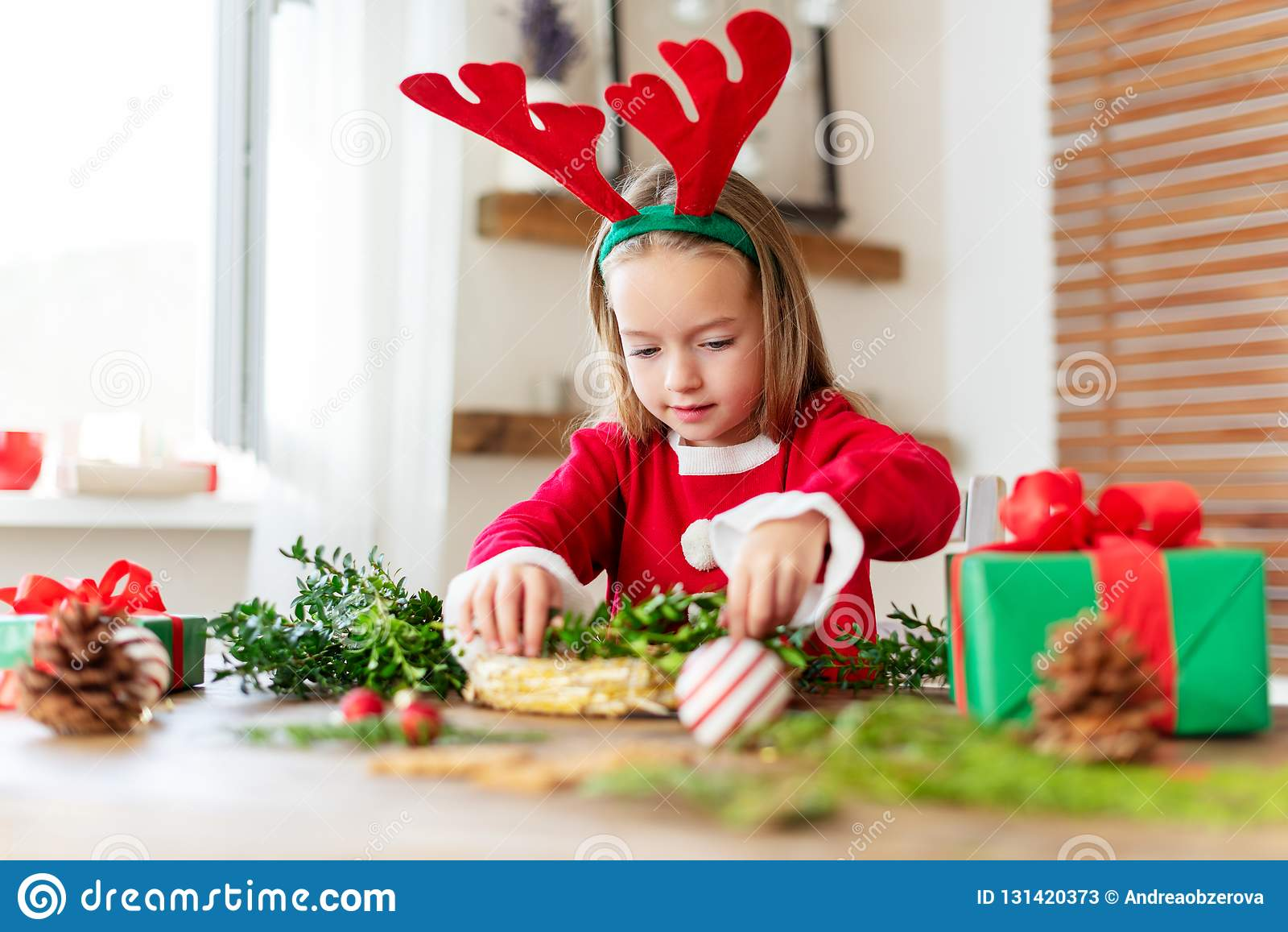 Cute preschooler girl dressed in reindeer costume wearing reindeer antlers making christmas wreath in living room.