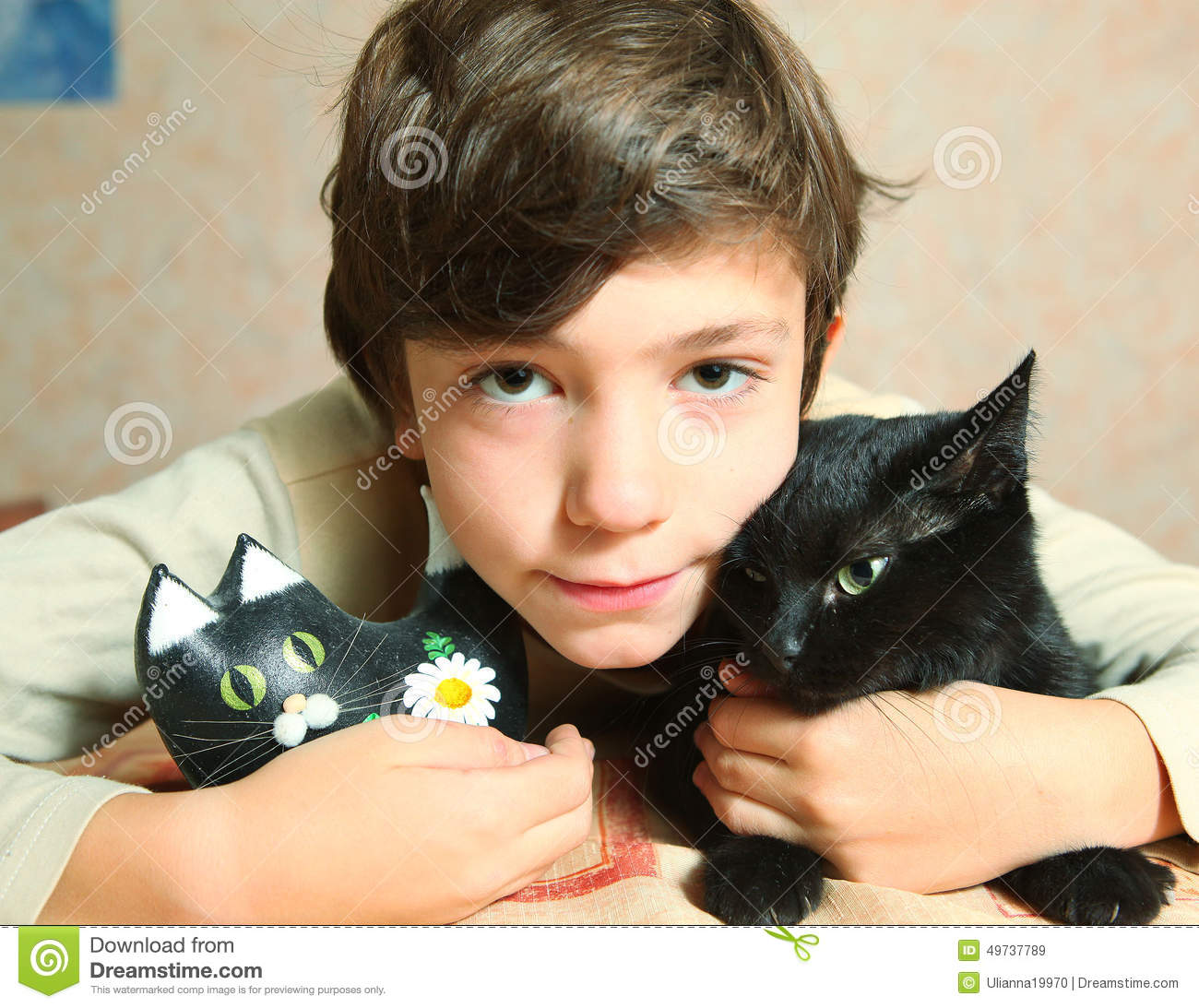 black preteen Cute preteen boy with black cat on the table Royalty Free Stock Images