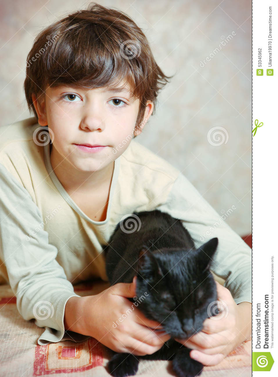 black preteen Cute preteen boy with black cat on the table
