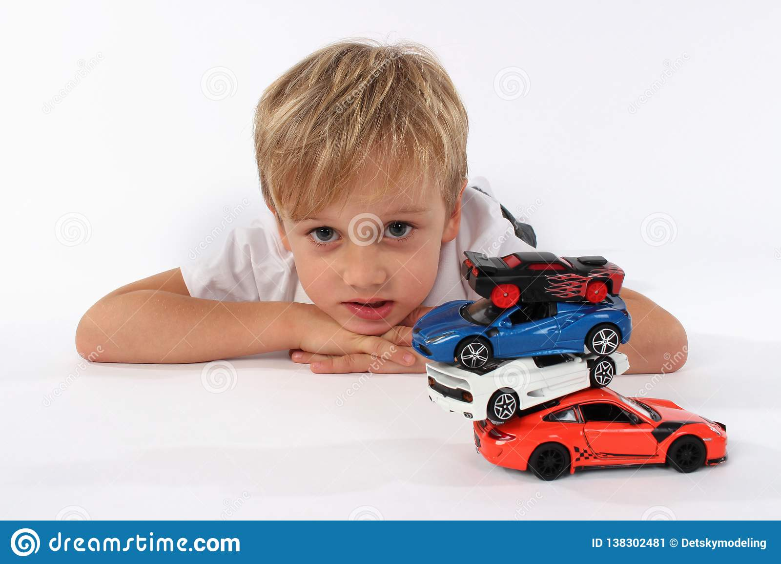 Cute preteen boy lying with a pile of car toys and making a confused look in his face
