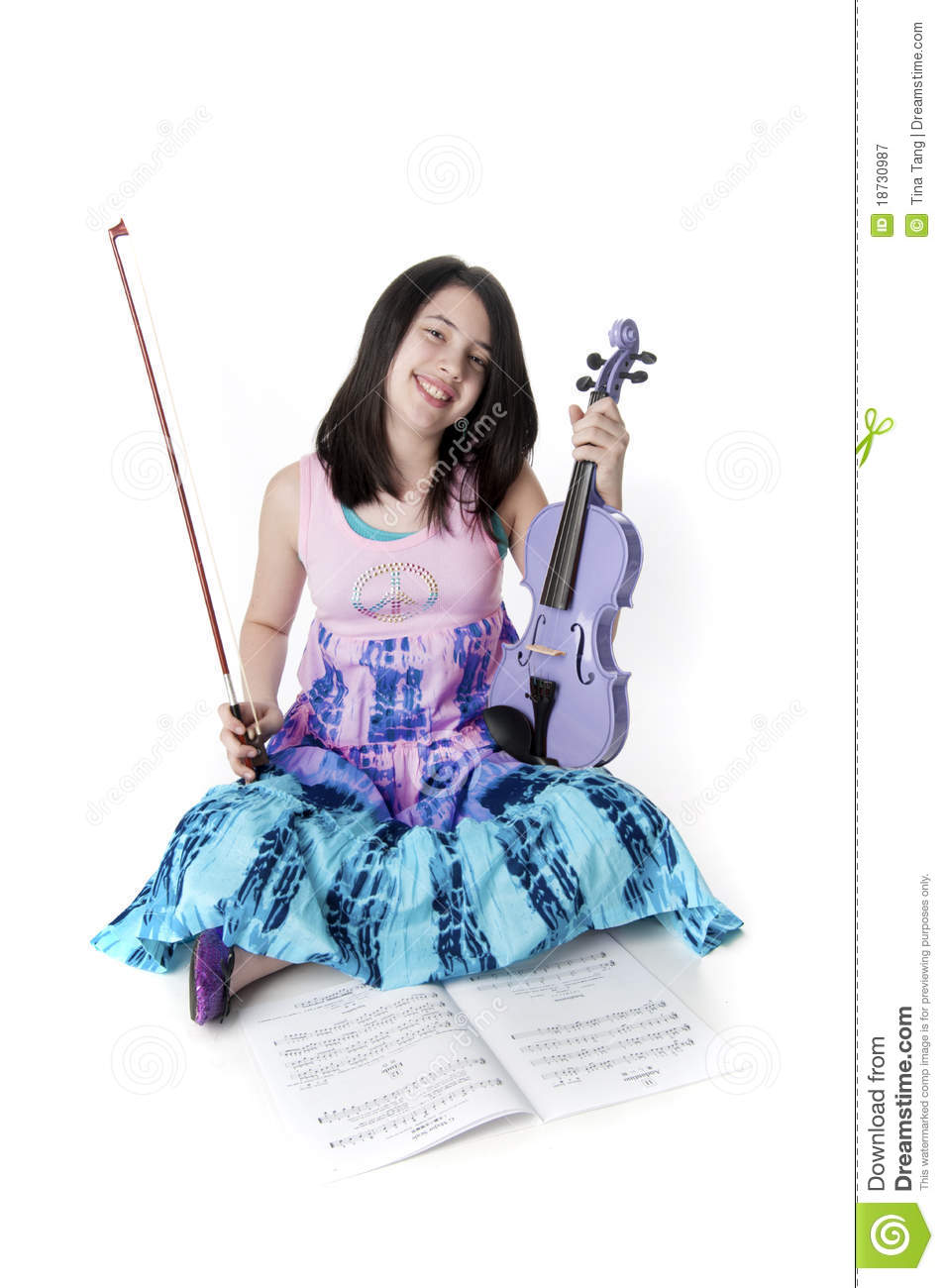 Preteen girl holding a purple violin in tie dye dress.