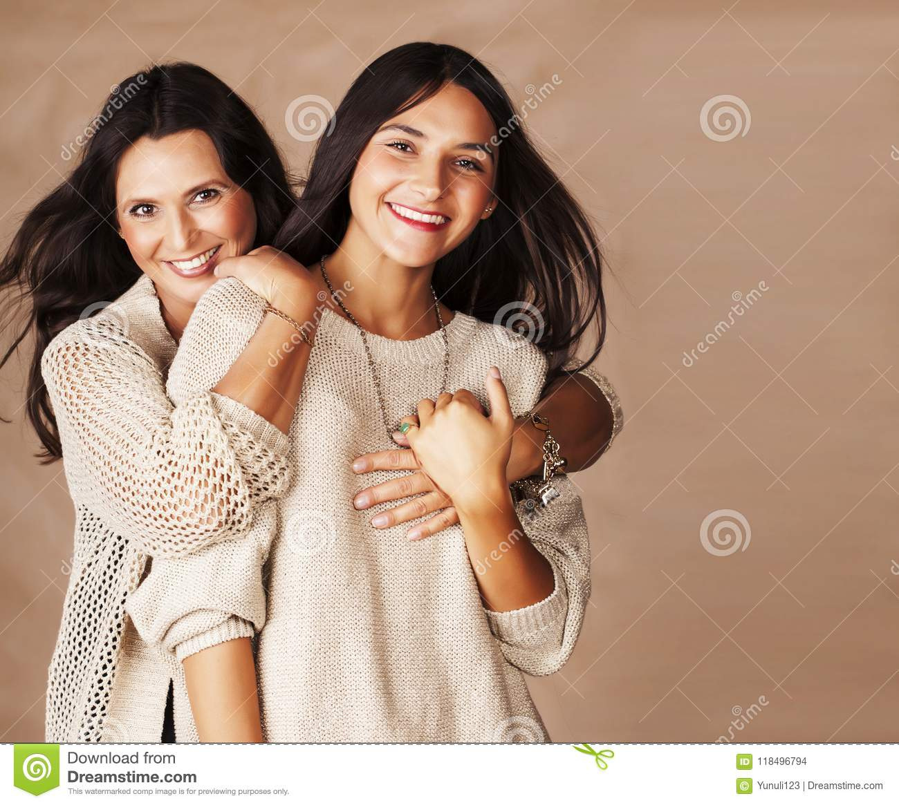 Cute pretty teen daughter with mature mothr hugging, fashion style brunette