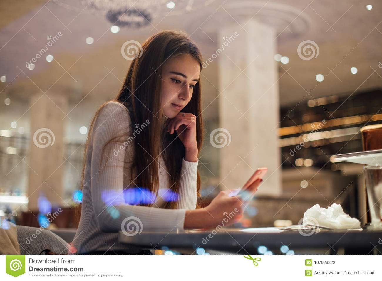 Cute and pretty young woman on smartphone in cafe