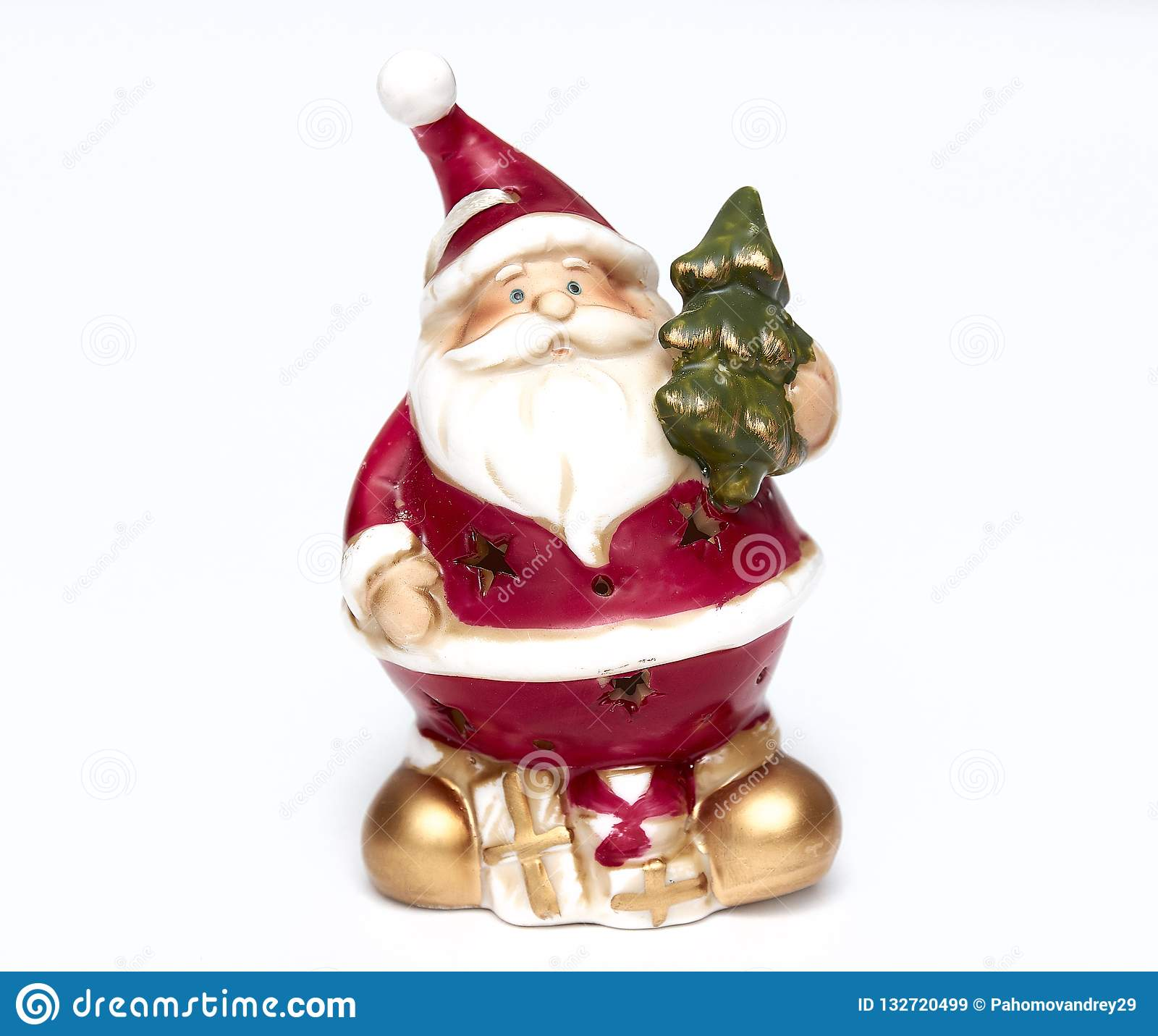 Cute Santa Claus doll with a Christmas tree in his hand. Adorable Santa Claus decorative toy, insulator on a white background.