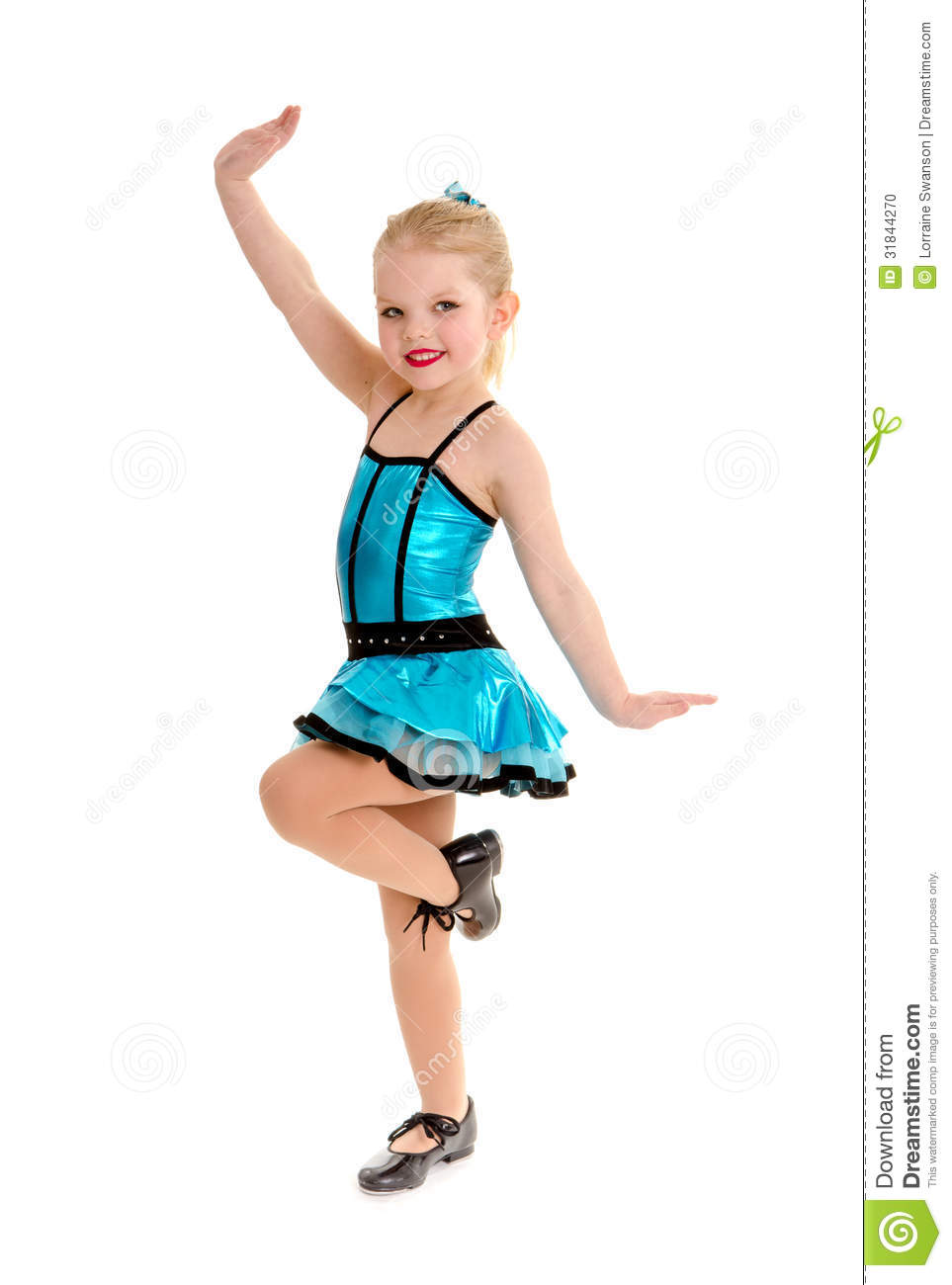 cute little girl tap dancer poses with leg lifted in tap shoes and