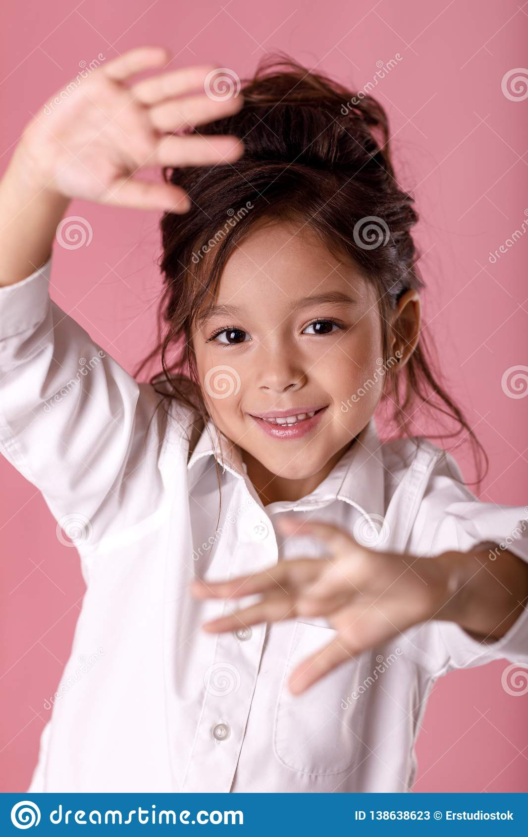 Cute scared little girl in white shirt making stop gesture on pink background. Human emotions and facial expression