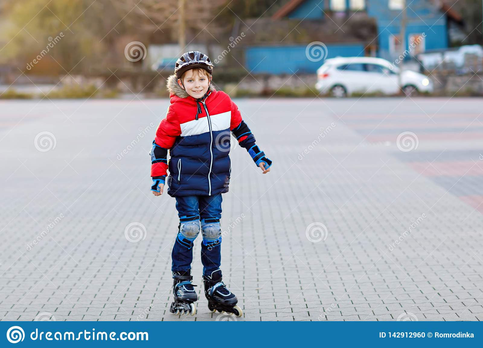Cute school kid boy skating with rollers in the city. Happy healthy child in protection safety clothes skating with