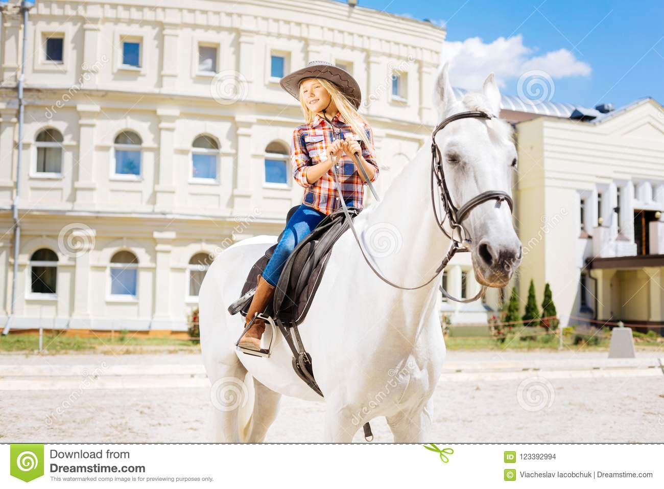 Cute schoolgirl fond of equestrianism riding horse on weekend