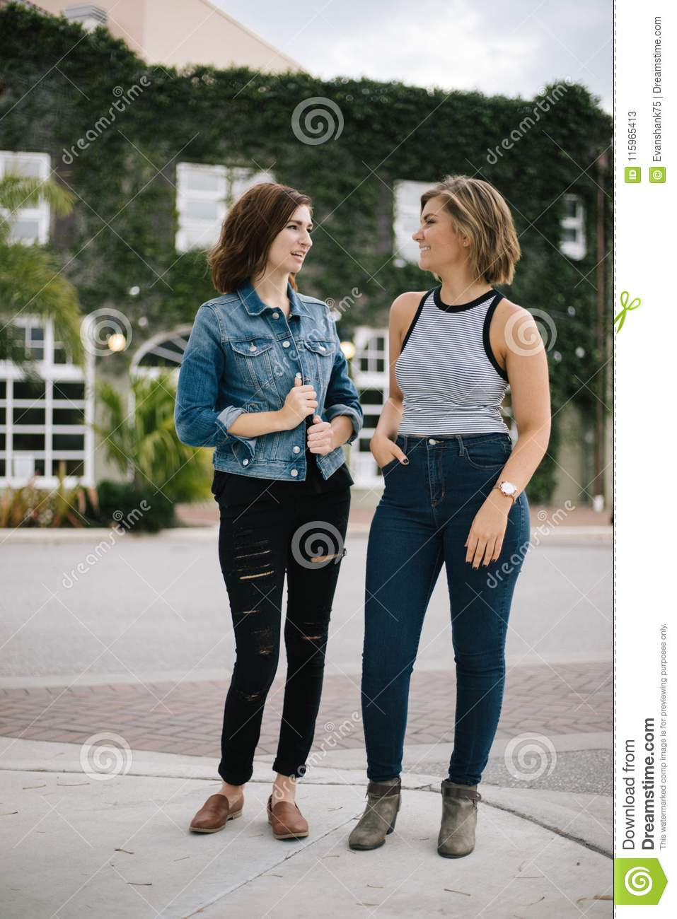 Attractive Young Female Best Friends Modeling and Having Fun in Front of Overgrown Urban Building