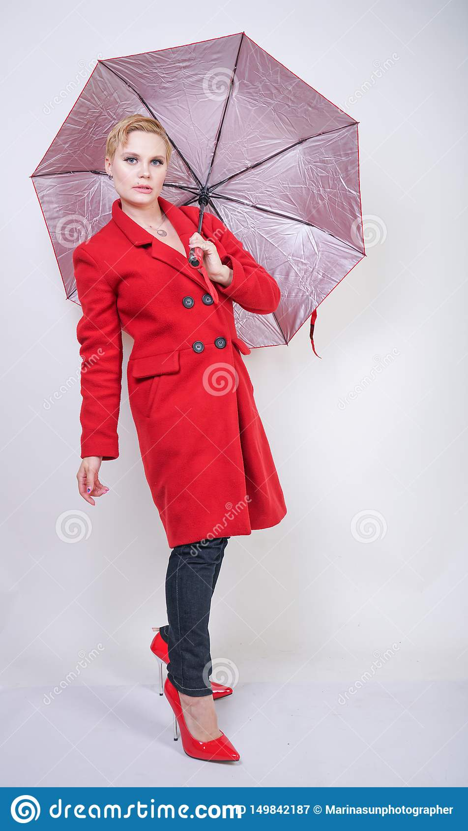 Cute short hair chubby girl in a modern city wool coat holding a red umbrella and posing on a white background in the Studio alone