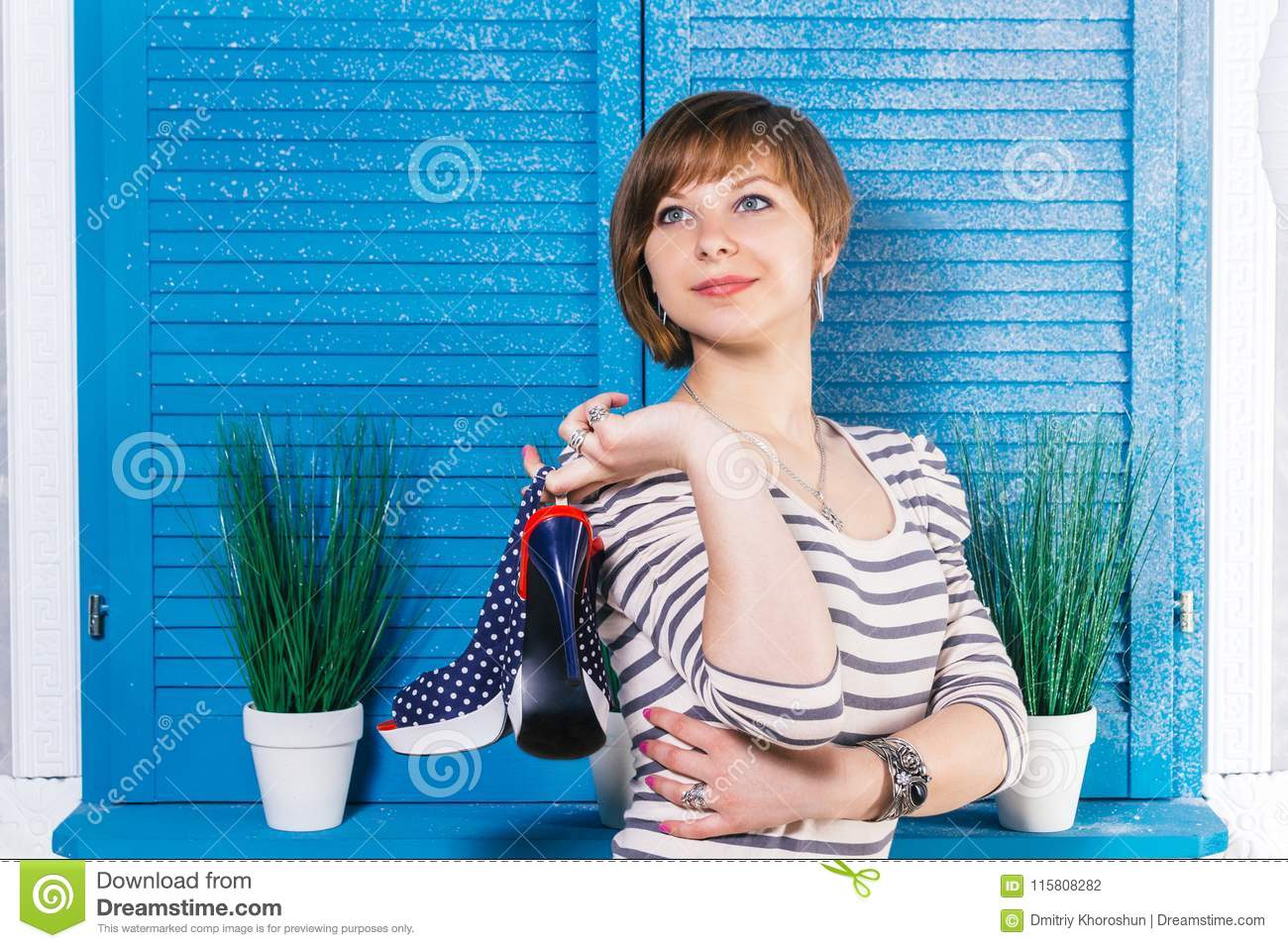 Cute short-haired european teen Girl holding her new high heeled dotted  shoes in front of blue jalousie window with green plants. Shopping concept  with copy ...