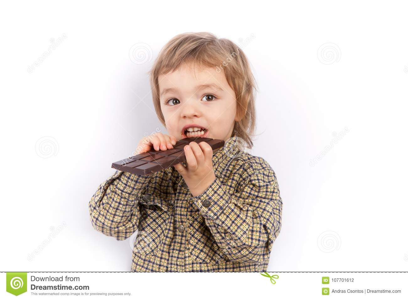 Cute small boy eating a chocolate bar