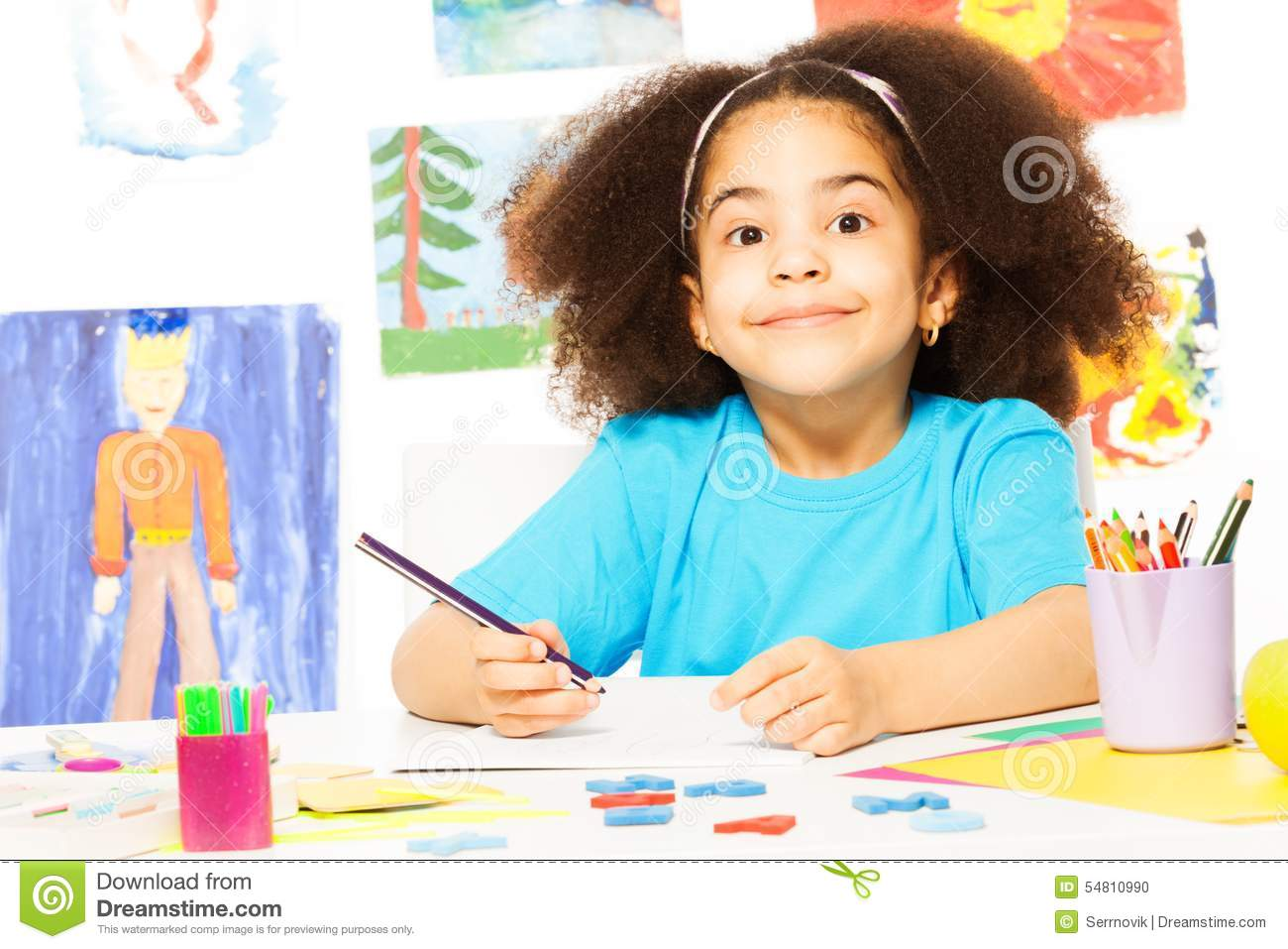 Cute smiling African girl writing at the desk