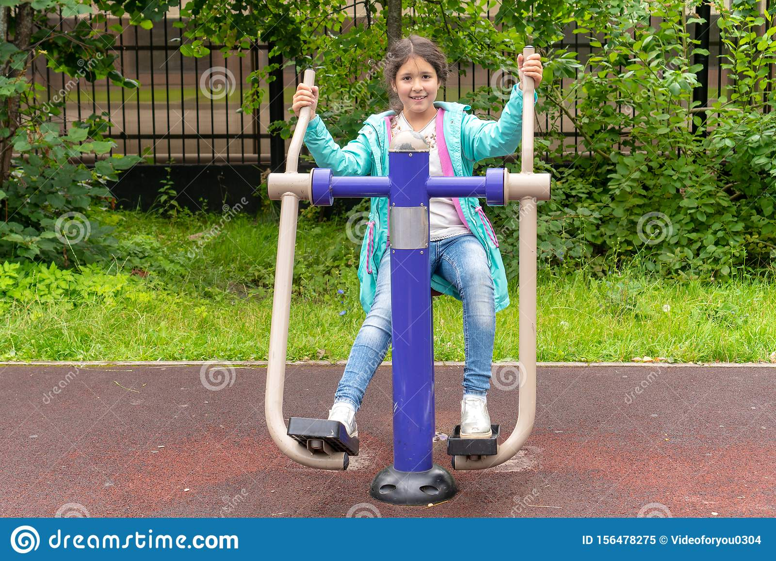 Cute smiling caucasian little girl sitting on trainer equipment outdoor sunset workout. Little girl doing exercises at the