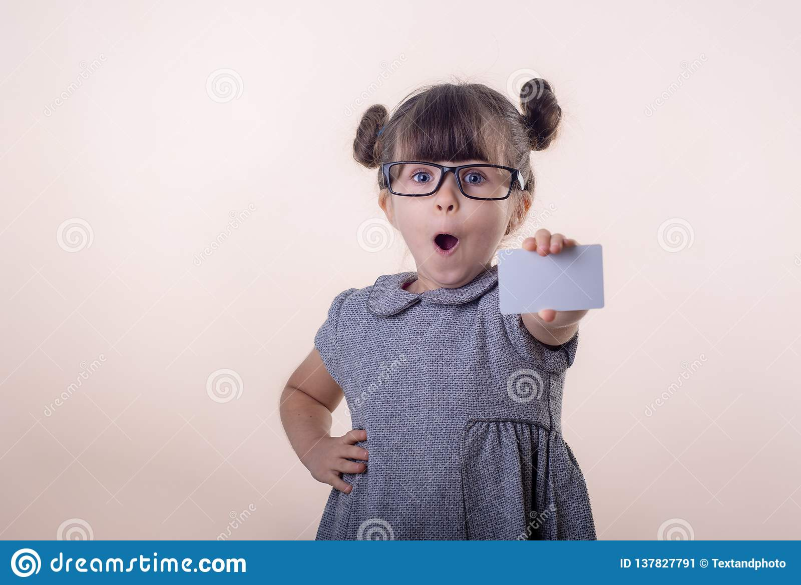 Cute smiling child with glasses holding bank card in her hands.