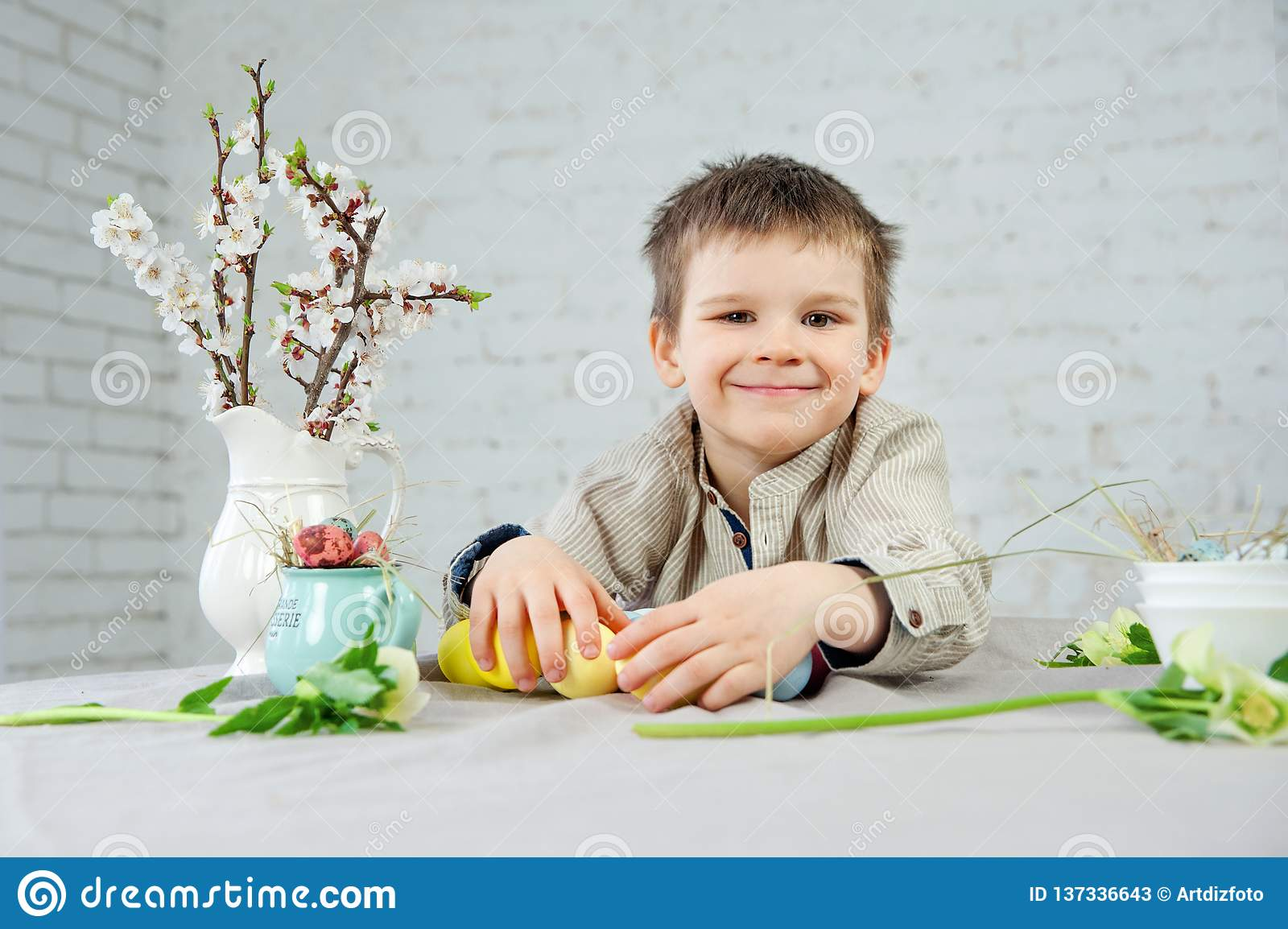 Cute smiling little boy painting Easter eggs on white background