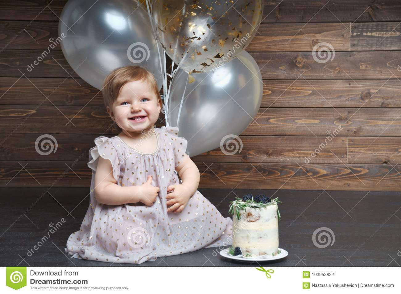 Cute smiling little girl celebrate her first birthday party with balloons and cake
