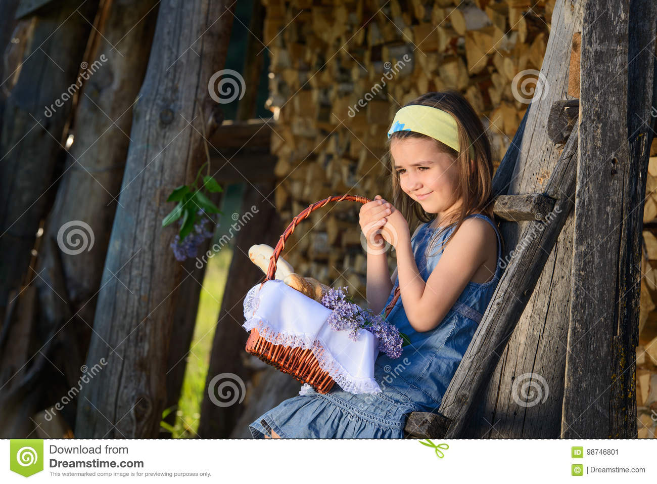 Cute smiling little girl holding a basket of flowers. Portrait in profile.