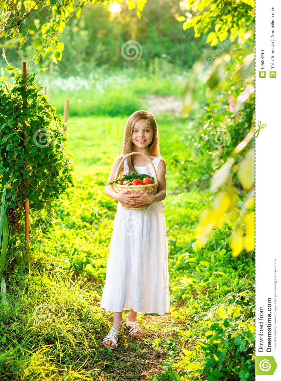Cute smiling little girl holds basket with fruit and vegetables