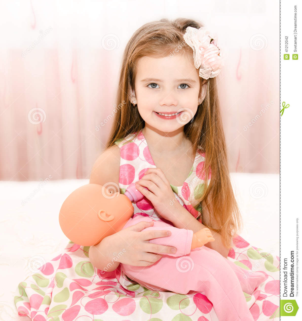 Adorable Little Girl Playing With Beach Toys During: Cute Smiling Little Girl Playing With A Doll Stock Photo