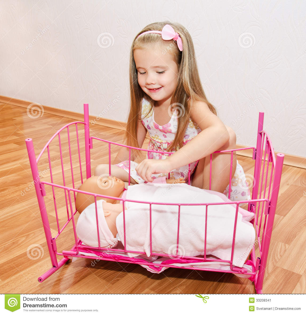 cute smiling little girl playing with her newborn baby dolls stock