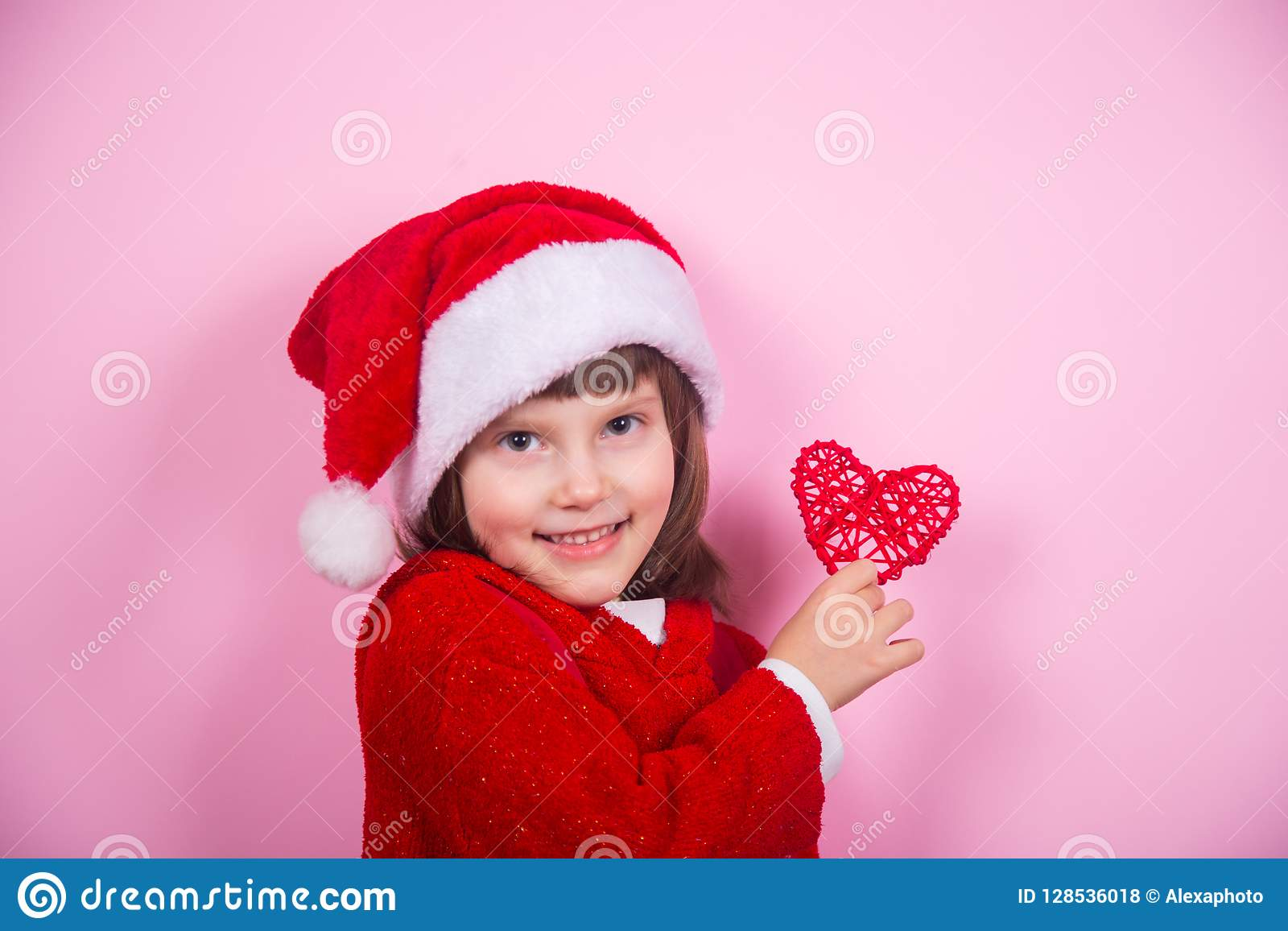 Cute smiling little girl in Santa hat and Christmas costume holding red  heart in studio on 9284b490c55