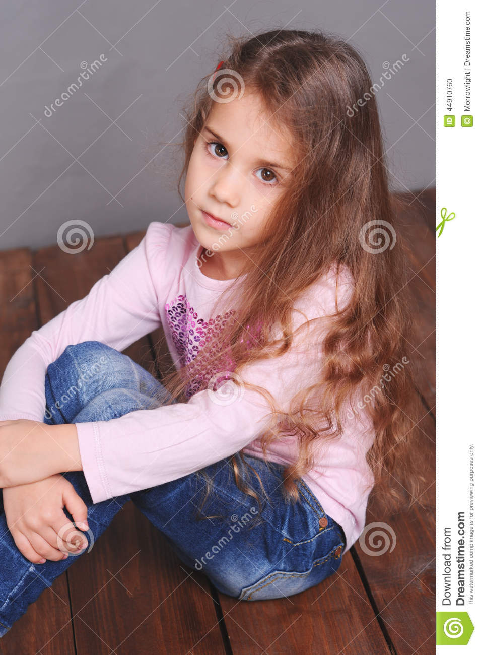 Cute Smiling Little Girl Sitting On Floor Stock Photo