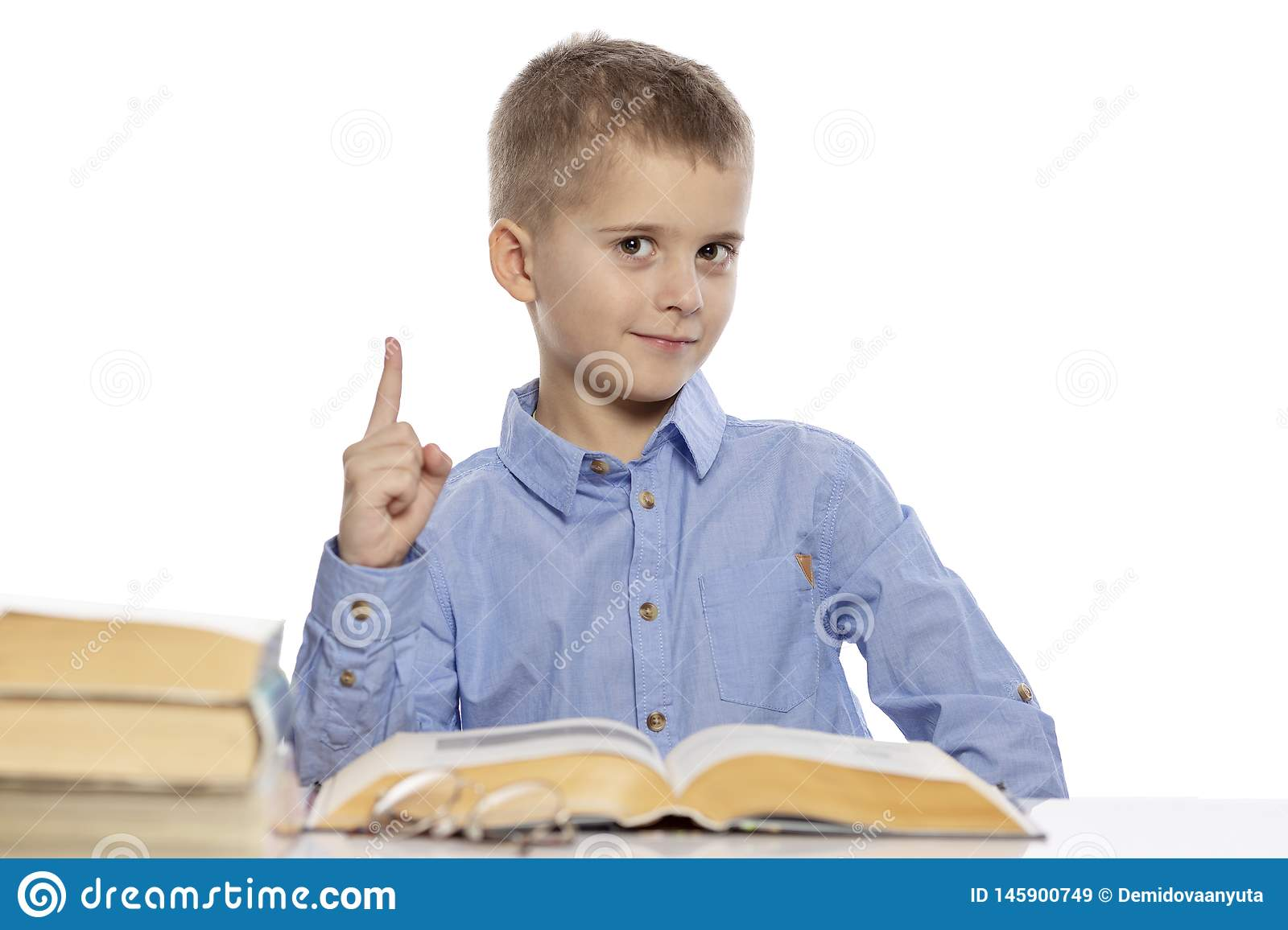 Cute smiling schoolboy sitting at the table with lessons. He raised his finger up. Isolated on a white background