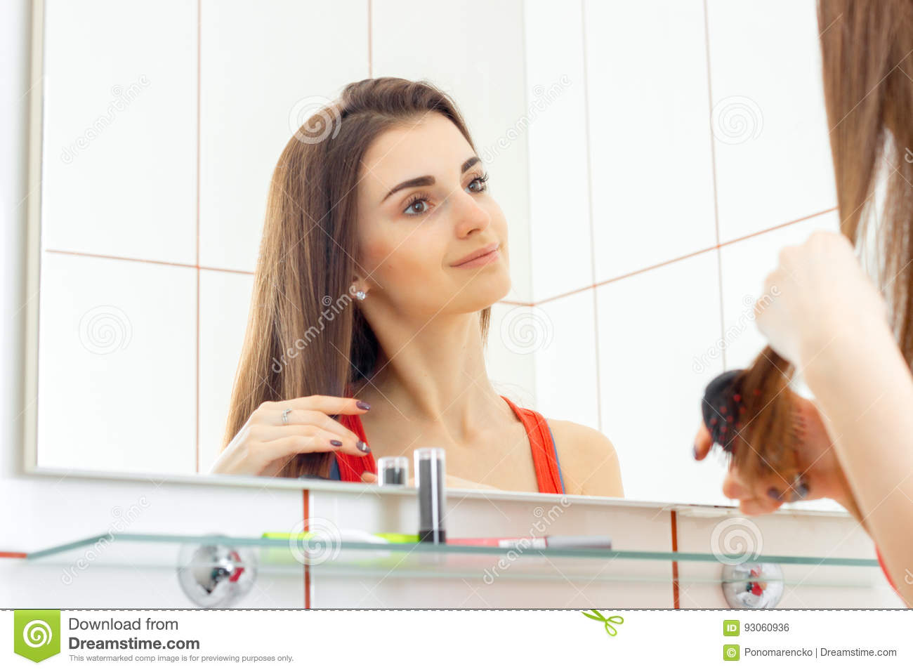 Cute Smiling Young Girl Stands In Front Of A Mirror And Combing Her