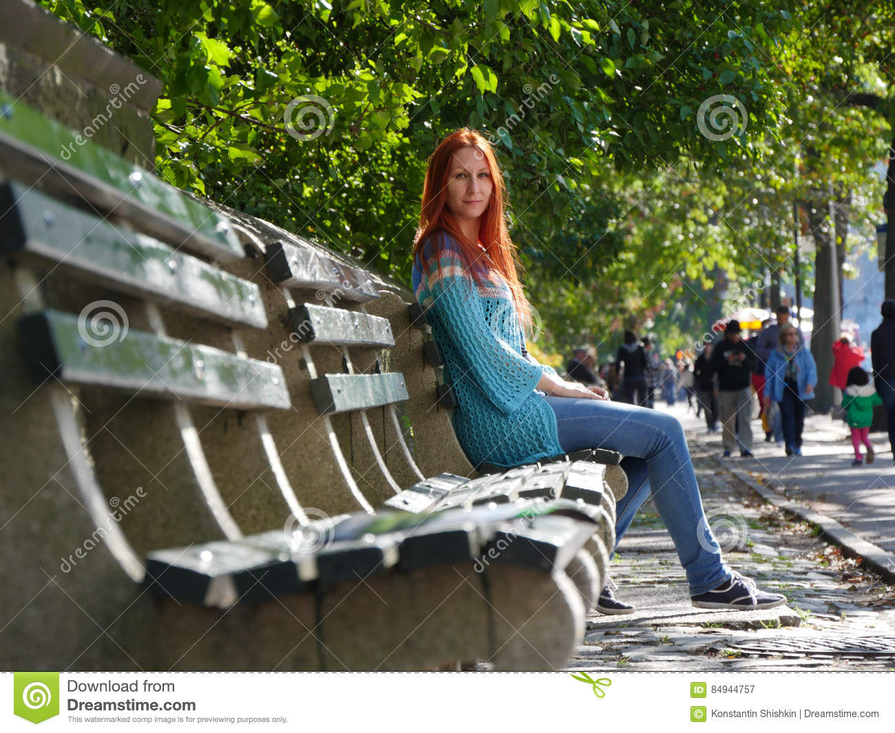 Cute Smiling Young Woman In Blue Jacket Sitting At Bench Central