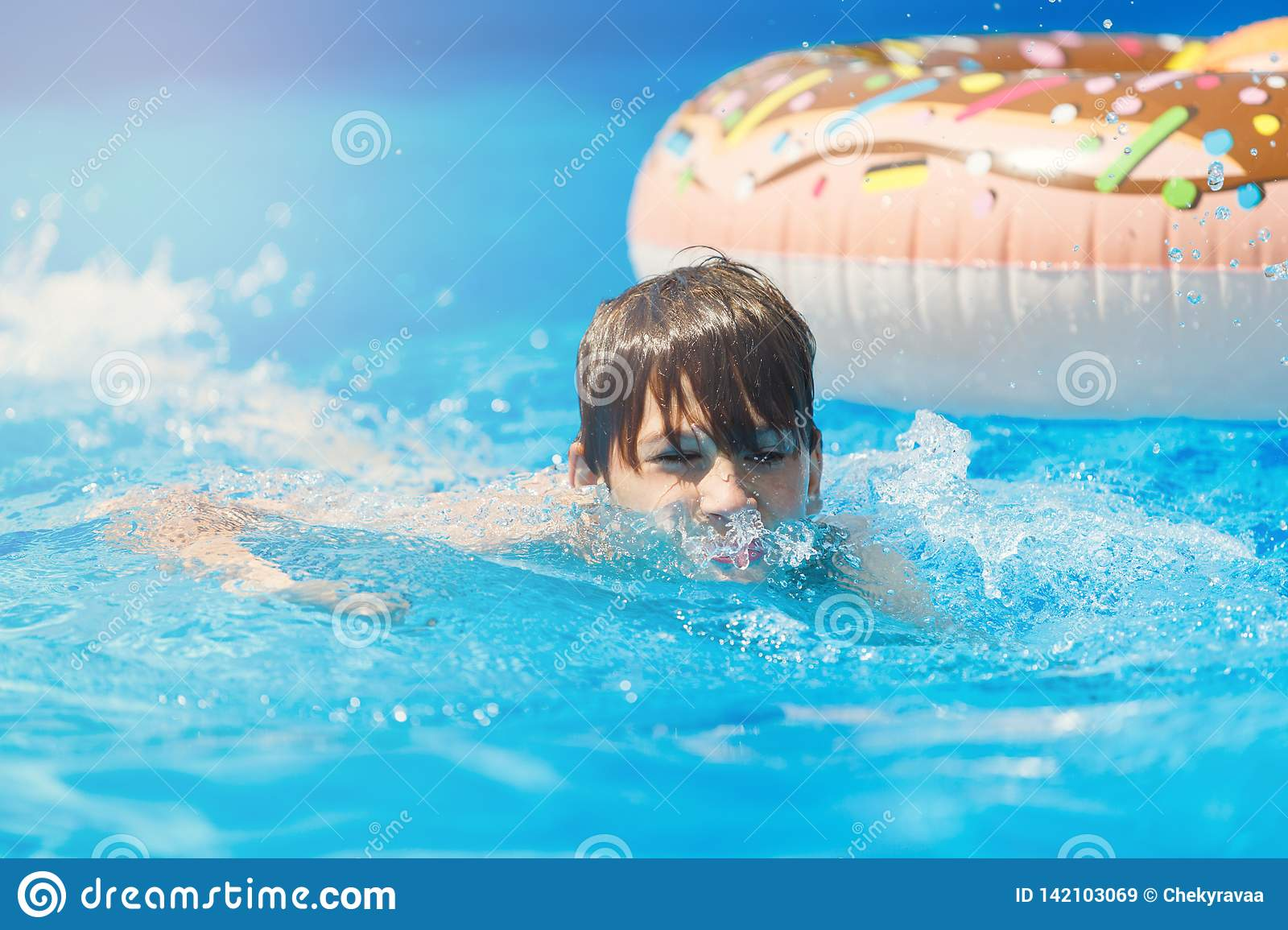 Cute sporty boy swims in the pool with donut ring and has fun, smiles, holds oranges. vacation with kids, holidays, active weekend