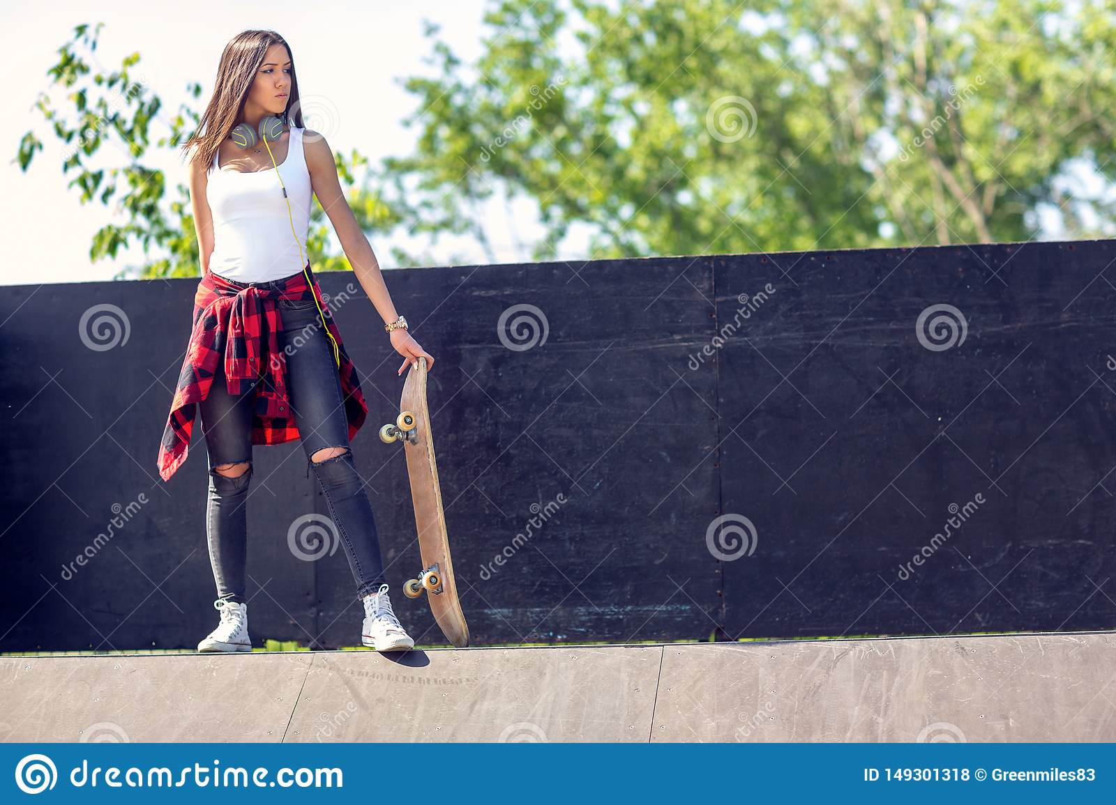 Sporty teen girl with skateboard. Outdoors, urban lifestyle