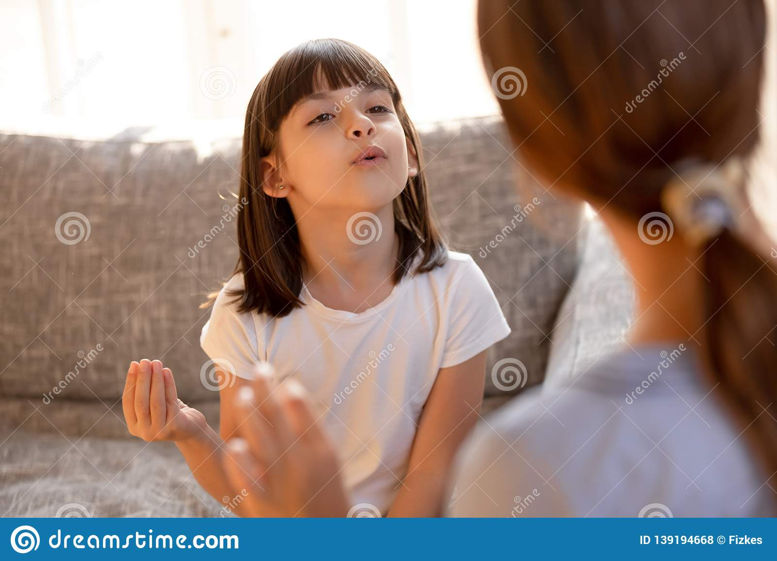 Cute stuttering child girl speaking doing exercises with speech therapist
