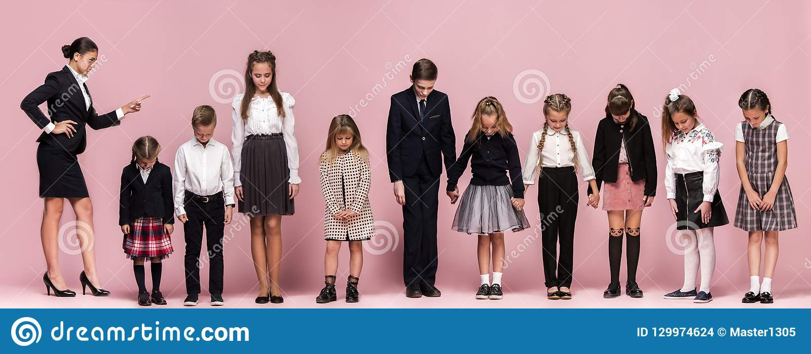 Cute stylish children on pink studio background. The beautiful teen girls and boy standing together