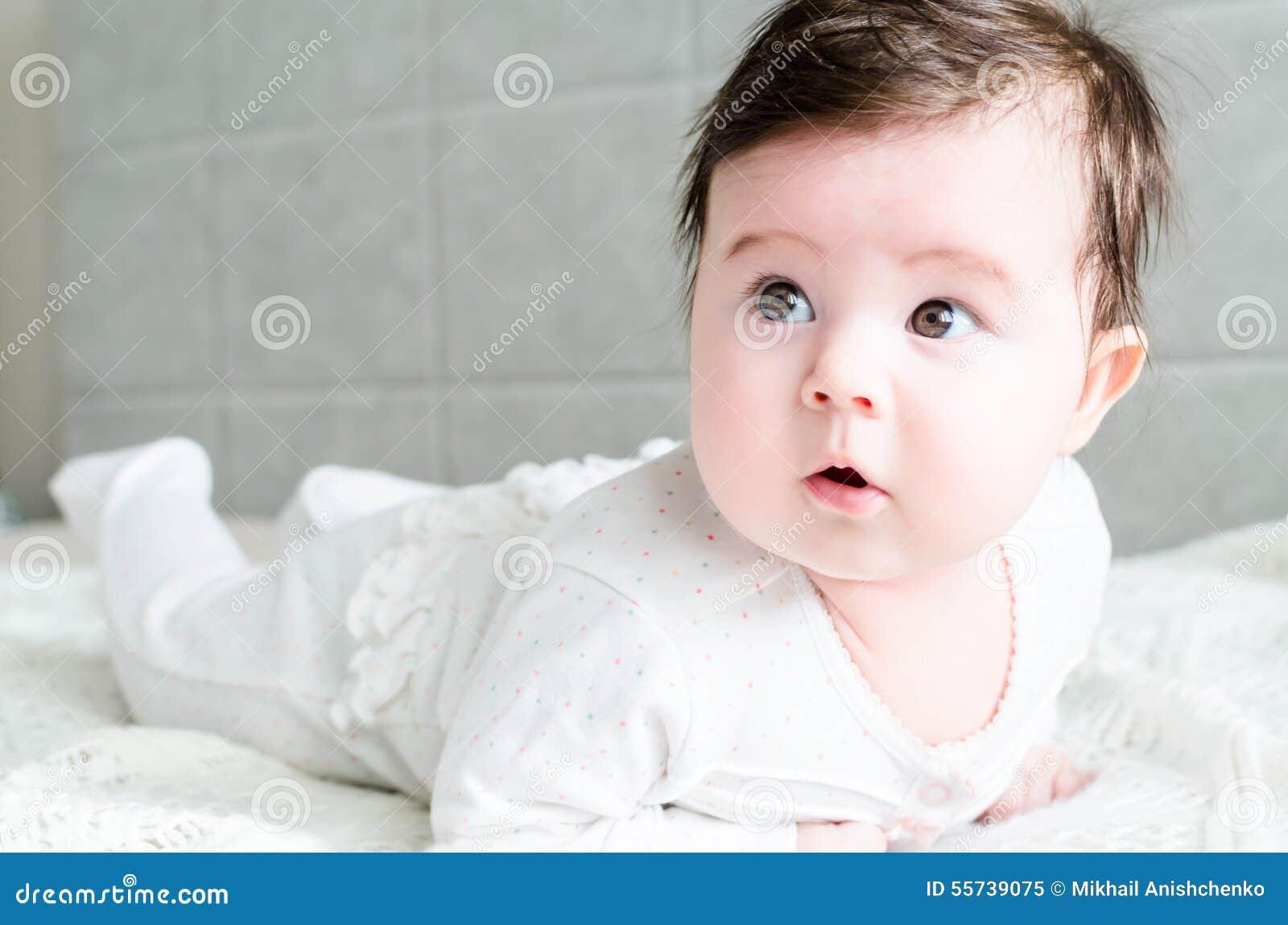 cute sweet little newborn baby girl lying on bed stock