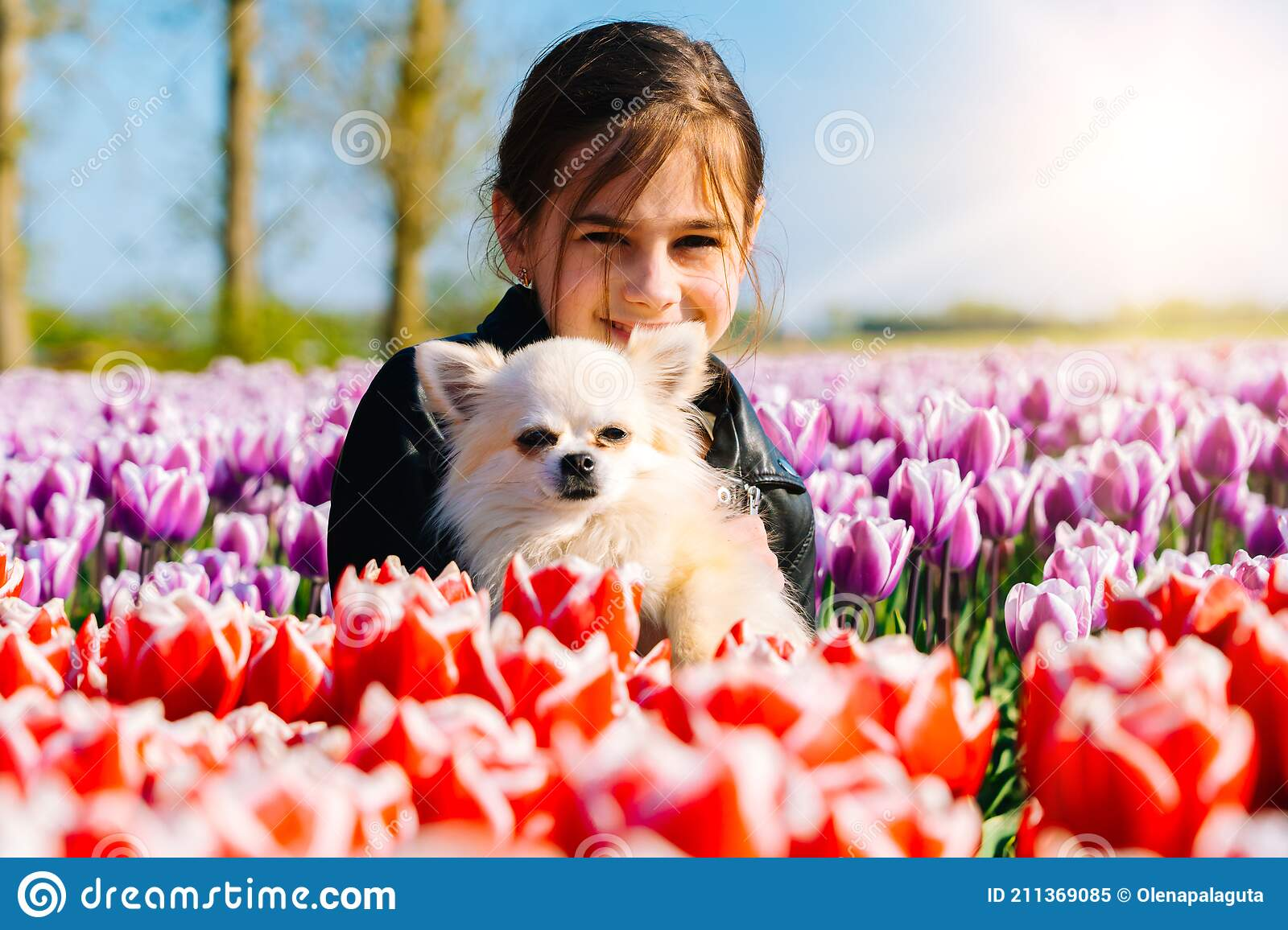Cute Teen Girl With Long Hair Smelling Tulip Flower On