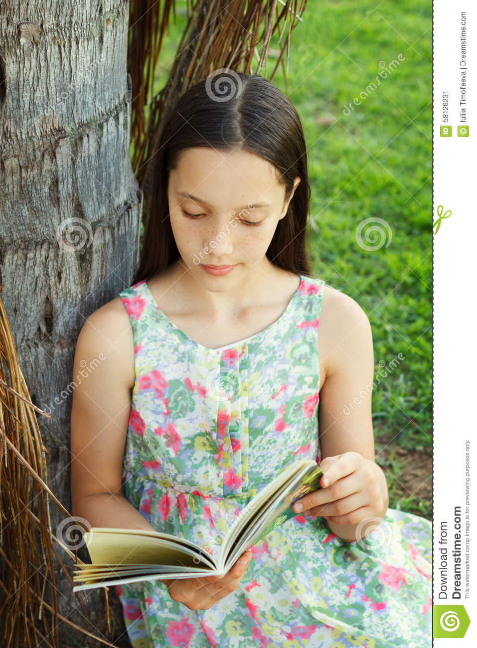 Cute Teen Girl Reading Book Sitting On Green Grass Stock