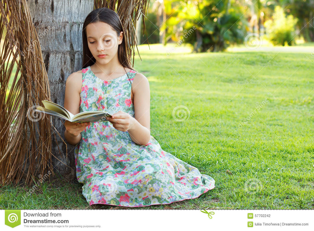 Cute teen girl reading book sitting on green grass stock for Cute teenager girls