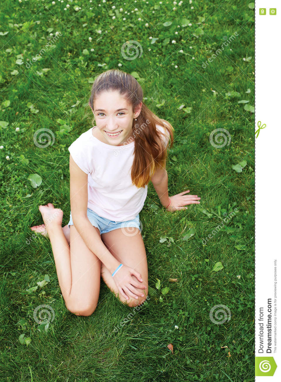 Cute Teen Girl Sitting On The Grass In The Park
