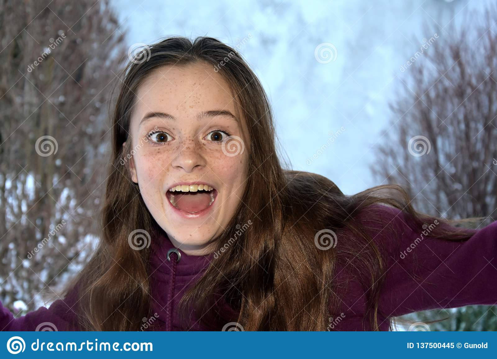 Cute teenage girl screams with joy